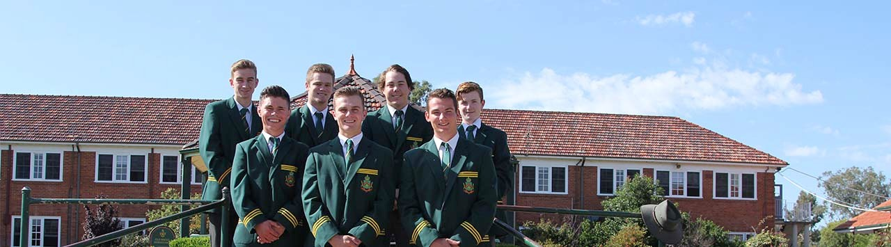 School captains and leaders standing in front centre lawn smiling